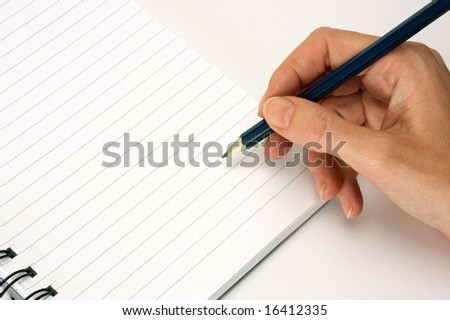 female hand writing with pencil on school note pad