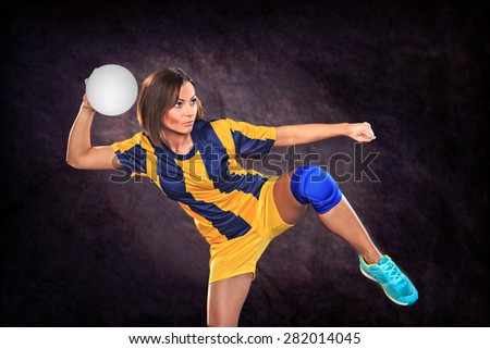 female handball player with a ball on the field - stock photo