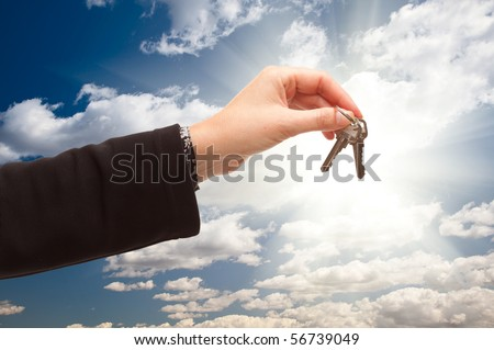Female Handing Over Keys on Dramatic Clouds and Sky with Sun Rays Behind. - stock photo