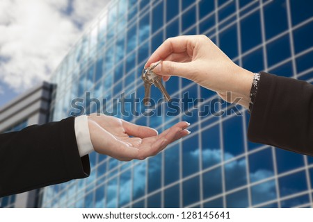 Female Handing Over the Keys to Other Woman in Front of Corporate Building. - stock photo