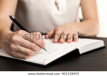 female hands a close up writing in the daily log - stock photo