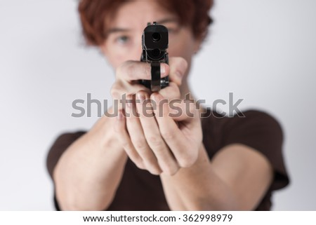 Female hands aiming a gun in the direction of a viewer.