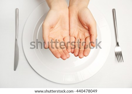 Female hands and empty plate on white background - stock photo