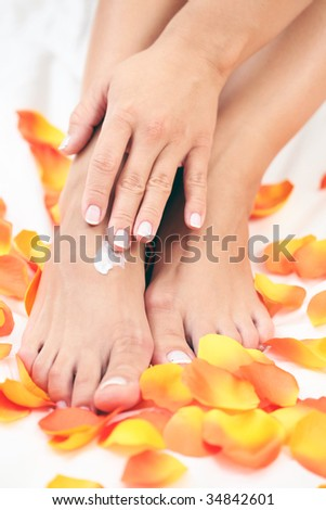 female hands and feet with petal of rose - beauty treatment
