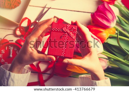 Female hands are holding a gift before wrapping near tulip flowes on white wooden background - stock photo