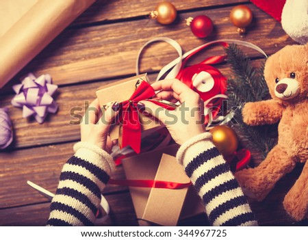 Female hands are wrapping a christmas gift on wooden background - stock photo