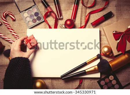 Female hands are wrapping cosmetics in christmas gifts on jute background