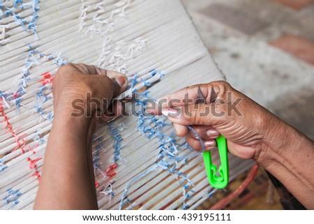 Female hands bind cotton dyed Indigo in Thailand. - stock photo