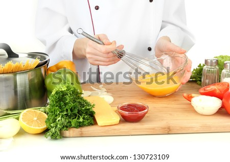 Female hands blending eggs in glass bowl - stock photo