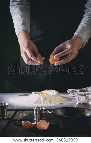 Female hands break the egg into flour for pasta on old wooden kitchen table. Vintage kitchenware and broken eggs at foreground. Dark rustic style with retro filter effect. See process series - stock photo