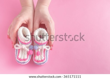 Female hands carefully holing baby shoes on pink background - stock photo