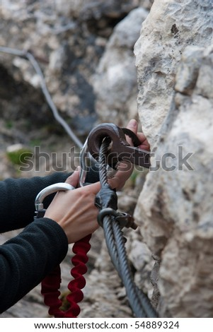 female hands caring for safety with a carabiner while climbing - stock photo