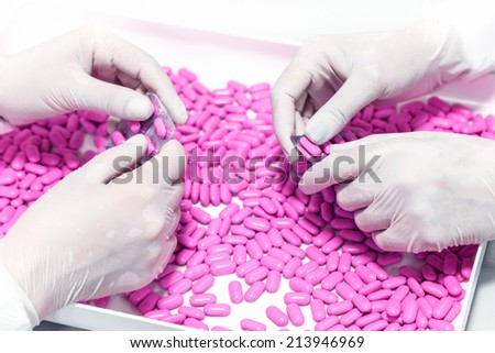 Female hands choosing, controlling the quality of a pills in a pharmaceutical factory.Unrecognizable people.Shallow doff.Macro, close up. - stock photo