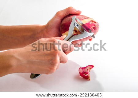 Female hands clean potatoes peeled - stock photo