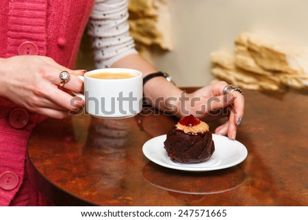 female hands closeup hold a cup of coffee and cake - stock photo