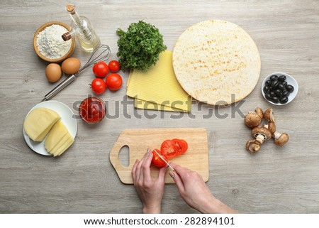 Female hands cooking pizza on wooden table, closeup - stock photo