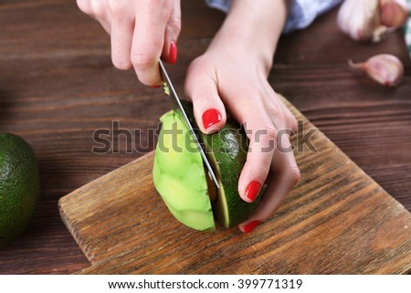 Female hands cutting an avocado in half, close up