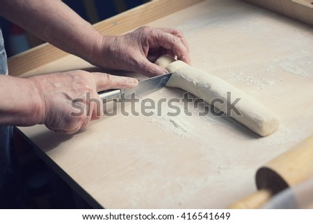 Female hands cutting dough with a knife