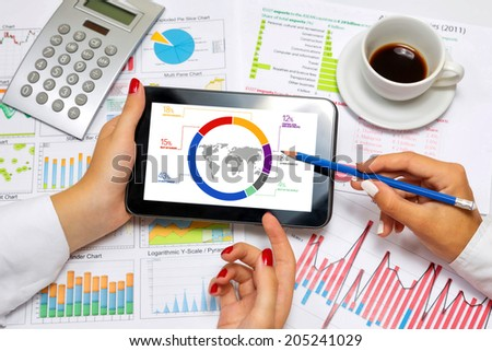 Female hands doing research on tablet, at business meeting. - stock photo