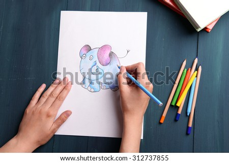 Female hands drawing picture on sheet of paper on wooden table background - stock photo