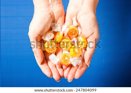 female hands filled with orange candies  - stock photo