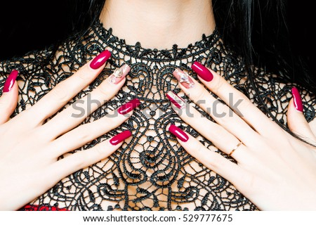 Female hands fingers with beautiful fingernail art manicure covered with red nail polish on black lace dress