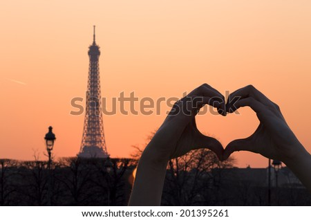 Female Hands Forming a Heart Shape at Sunset in front of the Eiffel Tower - stock photo