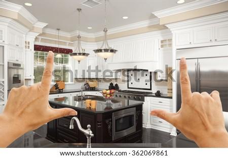 Female Hands Framing A Beautiful Custom Kitchen Interior. - stock photo