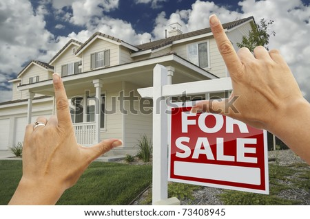 Female Hands Framing Home For Sale Real Estate Sign in Front of New House. - stock photo