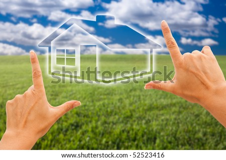 Female Hands Framing House Over Grass Field and Sky - stock photo
