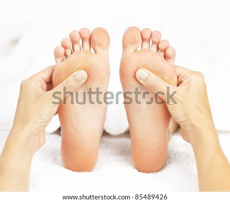 Female hands giving massage to soft bare feet - stock photo