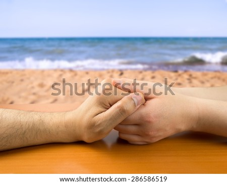 female hands grasping the concept of a man in love on the beach - stock photo
