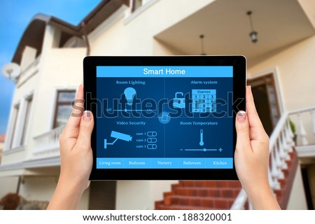 Female hands hold a tablet computer with system smart house on a screen on the background of the house - stock photo