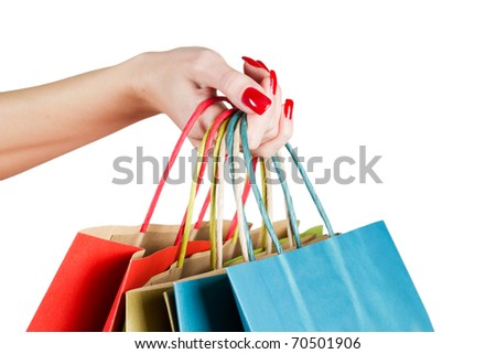 Female hands hold colorful shopping bag.