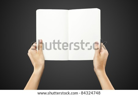 Female hands holding a blank white notebook. On a black background