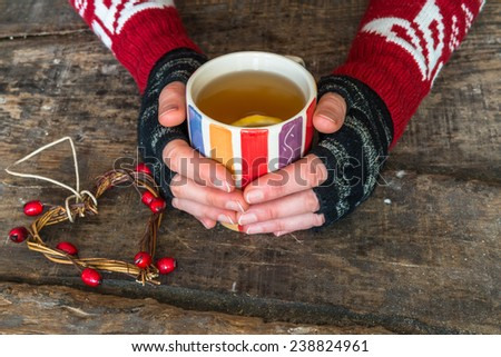 Female hands holding a cup of hot drink on rustic wooden table, close-up - stock photo