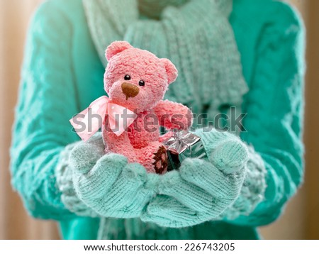 Female hands holding a cute teddy bear. Woman hands in teal mittens showing a teddy bear gift dresses in pink knitted hat and scarf. Cute Christmas present. Winter holidays concept.  - stock photo