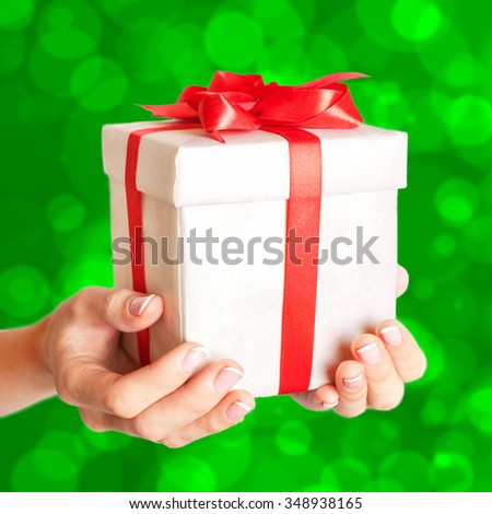 Female hands holding a gift box with a red bow on blurred bokeh green background. Time gifts. Selective focus on the present.  - stock photo