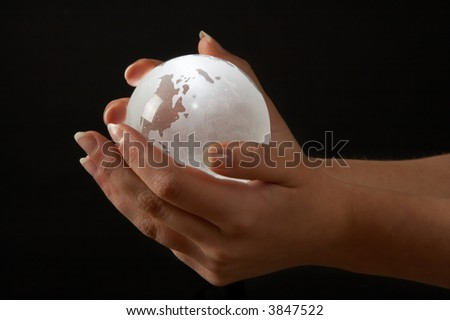 Female hands holding a glass backlit globe