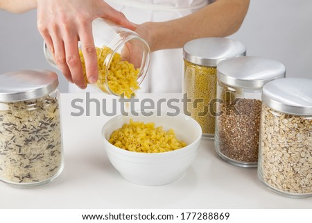 Female hands holding a pot with raw macaroni, grey background - stock photo