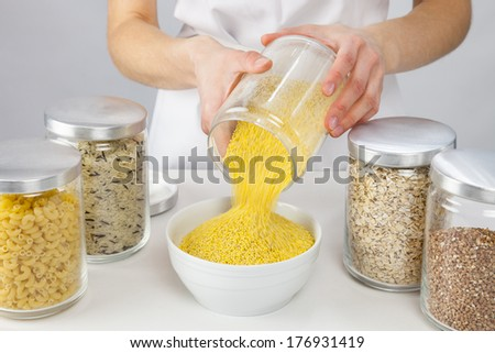 Female hands holding a pot with raw millet, grey background - stock photo