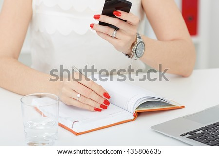 Female hands holding a silver pen and phone closeup.Business woman making notes at office workplace.Business job offer, financial success, certified public accountant concept.
