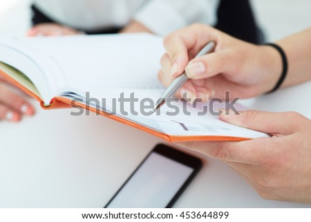 Female hands holding a silver pen closeup. Business woman pointing at the record in notebook. Business,  job offer, certified public accountant concept.