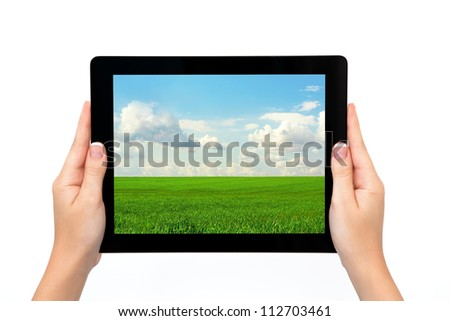 female hands holding a tablet touch computer gadget with the image of green grass and blue sky