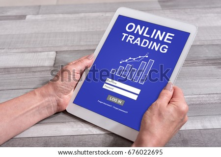Female hands holding a tablet with online trading concept
