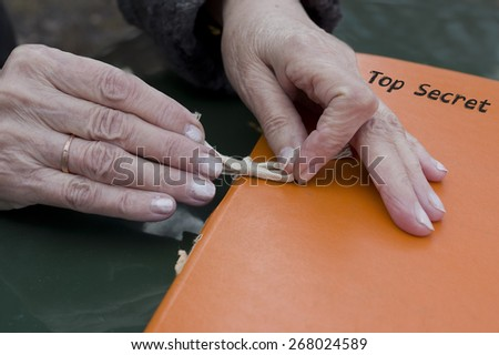 Female hands holding an orange retro looking folder, marked as Top Secret, concept of secrecy - stock photo