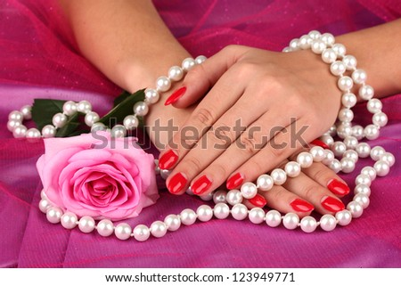 Female hands holding beads on color background - stock photo