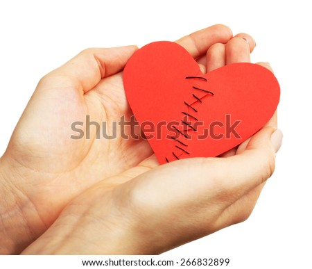 Female hands holding broken heart stitched from two pieces isolated on white - stock photo