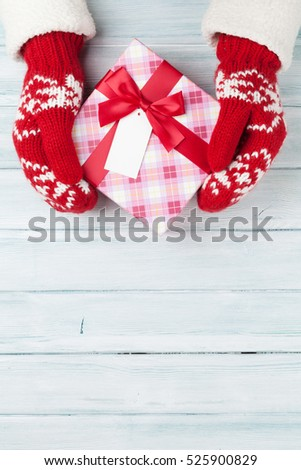 Female hands holding christmas gift above wooden table. Top view with copy space