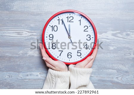 Female hands holding clock on a table. - stock photo